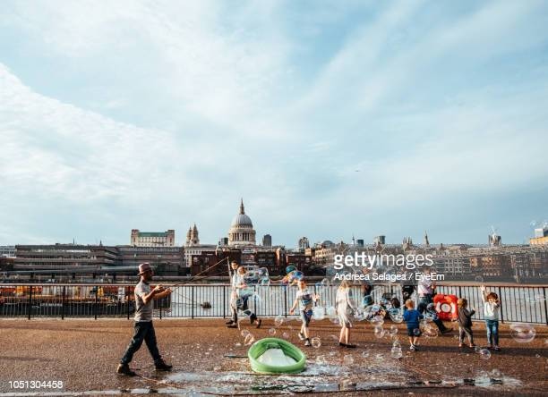 People With Bubbles On Street Against Sky In City