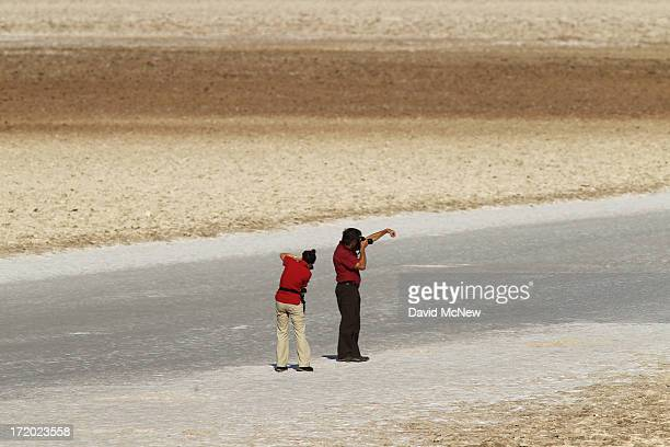 People with cameras walk on the salt flat at Badwater Basin the lowest point in the nation at 282 feet below sea level during a hot time of day as a...