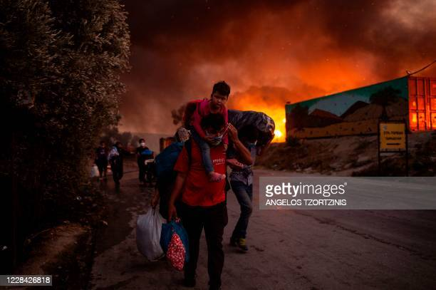 People with children flee flames after a major fire broke out in the Moria migrants camp on the Greek Aegean island of Lesbos, on September 9, 2020....