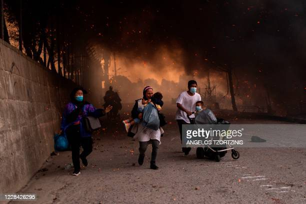 People with children flee flames major fire broke out in the Moria migrants camp on the Greek Aegean island of Lesbos, on September 9, 2020. -...