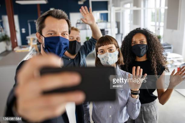 people with face masks back at work taking selfie - new normal concept stock pictures, royalty-free photos & images