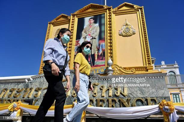 People with face masks walk pass a large portrait of Thailand's King Maha Vajiralongkorn near the Grand Palace in Bangkok on January 27, 2020. -...