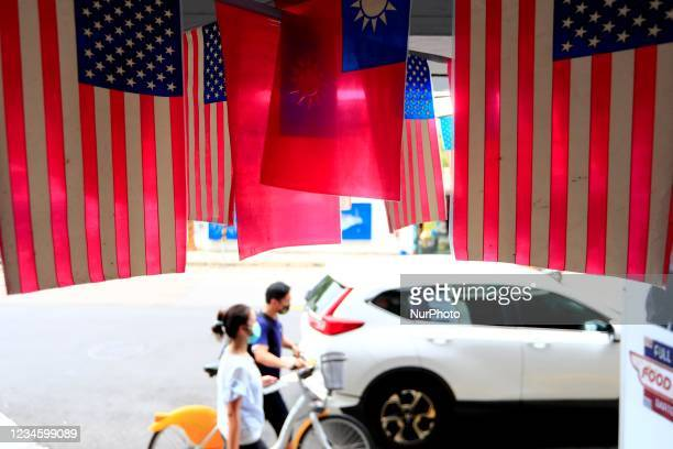 People with face masks walk past US-Taiwan which are hung outside a restaurant , amid USs ever-changing partnership with Taiwan and the escalating...