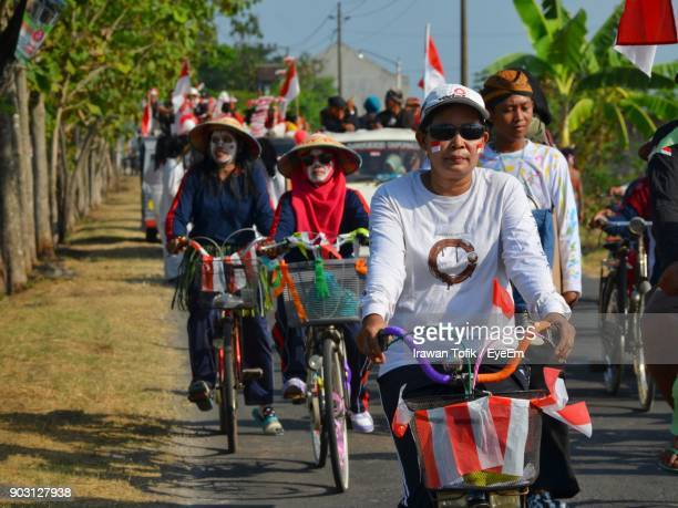 people with face paint riding bicycles - indonesia flag stock photos and pictures