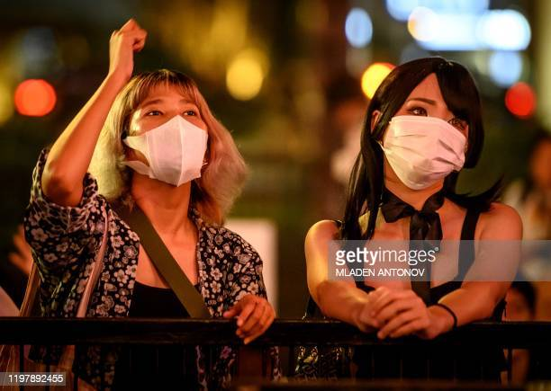 People with facemasks watch a live concert in Bangkok on February 1 2020 The World Health Organisation declared a global emergency over the new...