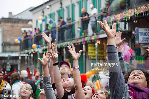 people with hands raised celebrating mardi gras on bourbon street - mardi gras party stock photos and pictures