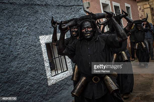 People with his face covered in oil and soot and carrying bull horns representing a devil join a carnival festival on February 14 2015 in Luzon Spain...