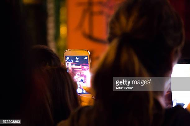People with his smartphones with bright screen in the night taking pictures for sharing on the social media networking websites