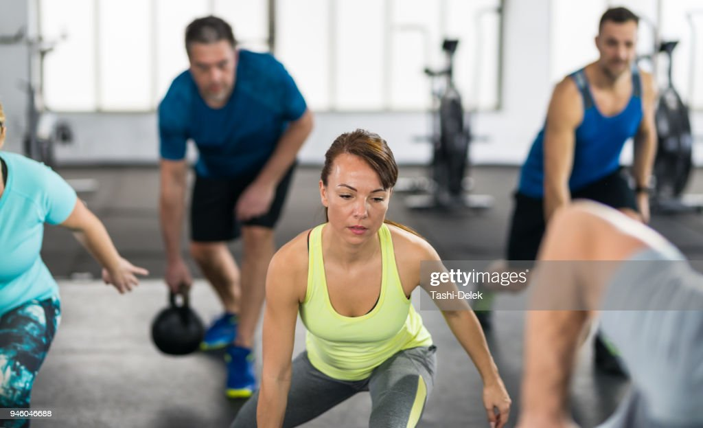 People With Kettlebells Squatting : Stock Photo