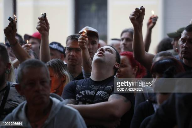People with lighters are pictured after a mourning march in Koethen eastern Germany on September 9 2018 German officials pleaded for calm on...