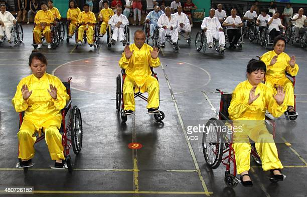 People with lowerlimb disabilities sitting in wheelchairs play Tai Chi Chuan in Xuanhua District on July 15 2015 in Zhangjiakou Hebei Province of...
