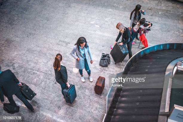 people with luggage by conveyor belt at airport - baggage claim stock pictures, royalty-free photos & images