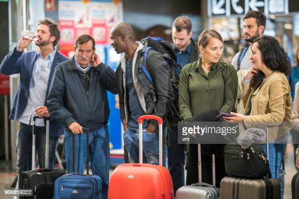 People with luggage waiting at an airport check-in area