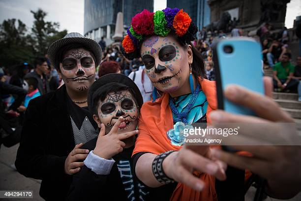 People with make up take selfie during Procession of the Catrinas in Mexico City Mexico on October 25 2015 The Catrina is a figure of a skeleton...