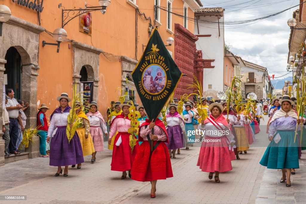 People with multicolored dresses and hats marching during the celebration of the Palm Sunday of Easter at Ayacucho city, Peru. : Stock Photo