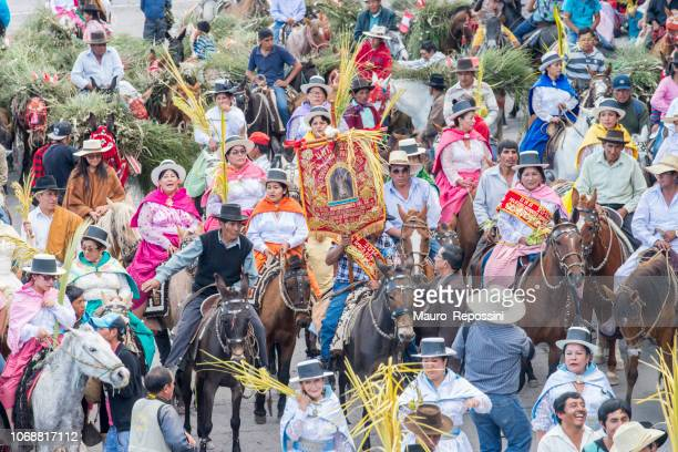People with multicolored dresses and hats riding horses during the celebration of the Palm Sunday of Easter at Ayacucho city, Peru.