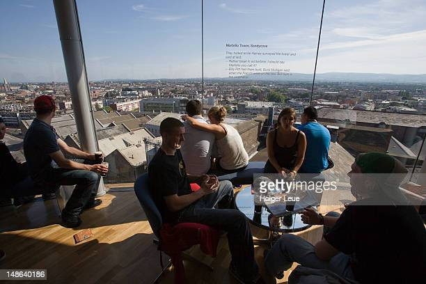 People with pints of Guinness in Gravity Bar at Guinness Storehouse brewery.