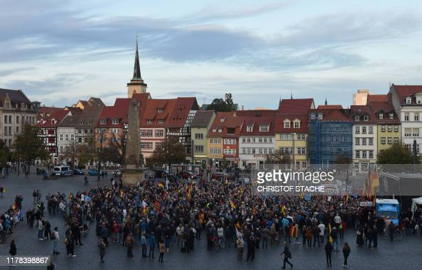 People with placards and German nationals flags take part in an election campaign event of the AfD party on October 26, 2019 in Erfurt, eastern...