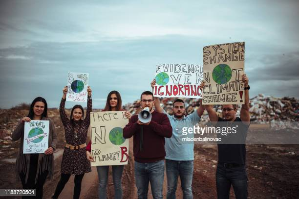 mensen met borden en posters over wereldwijde staking voor klimaatverandering - klimaat stockfoto's en -beelden
