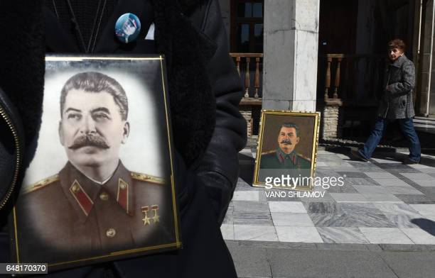 TOPSHOT People with portraits of Soviet leader Joseph Stalin gather outside his museum in his native town of Gori some 80 kms outside Tbilisi on...