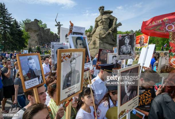 People with portraits of World War Two soldiers take part in the Victory Day celebrations at the Mamayev Kurgan WWII memorial complex with the statue...