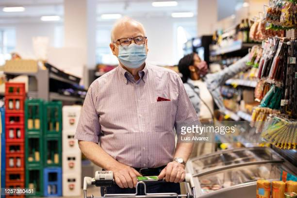 people with protective face mask at grocery store - personne secondaire photos et images de collection