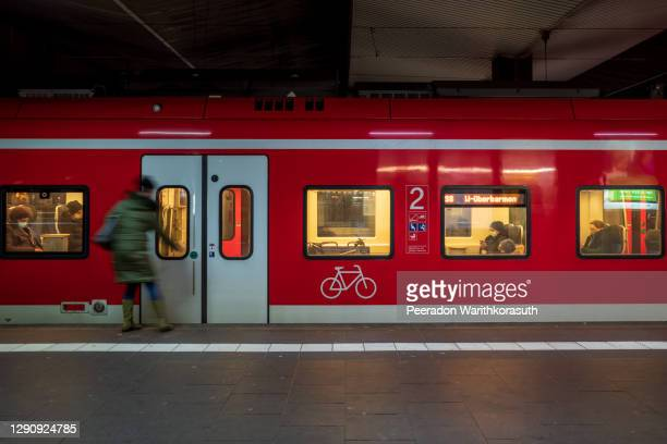 people with protective face mask get into train in germany. - safety american football player stock pictures, royalty-free photos & images
