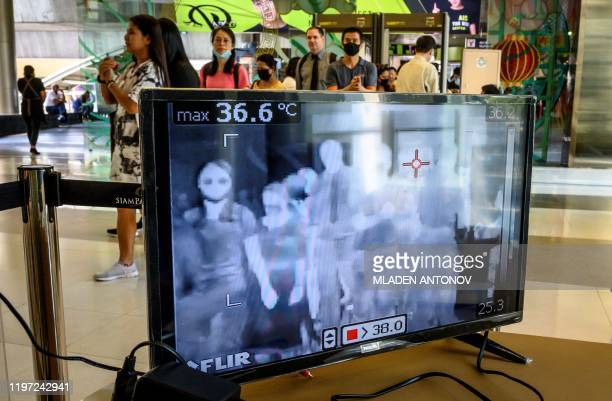 People with protective face masks pass in front of a thermal scanner as they enter a shopping mall in Bangkok on January 29, 2020. - Thailand has...