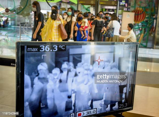 People with protective face masks pass in front of a thermal scanner as they enter a shopping mall in Bangkok on January 29 2020 Thailand has...