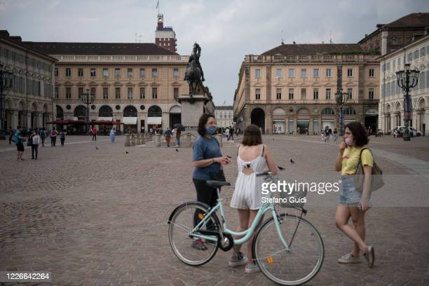 People with protective mask walks on Piazza San Carlo on May 23 2020 in Turin Italy Restaurants bars cafes hairdressers and other shops have reopened...