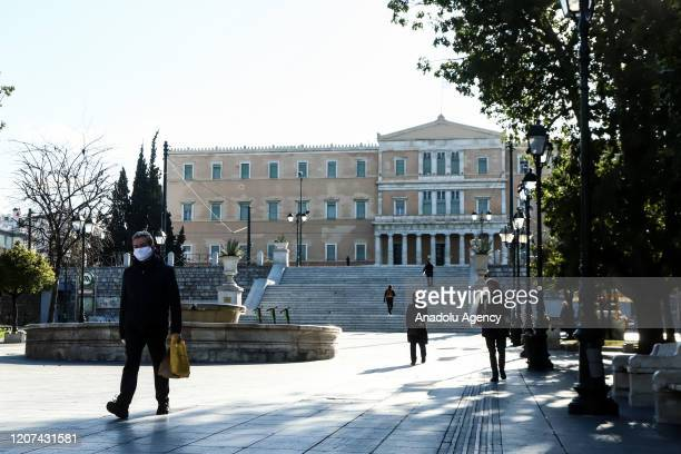 People with protective masks are seen in front of the Greek Parliament building due to coronavirus outbreak at Syntagma Square in Athens, Greece on...