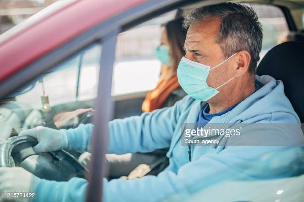people with protective masks riding in car together - driving mask stock pictures, royalty-free photos & images