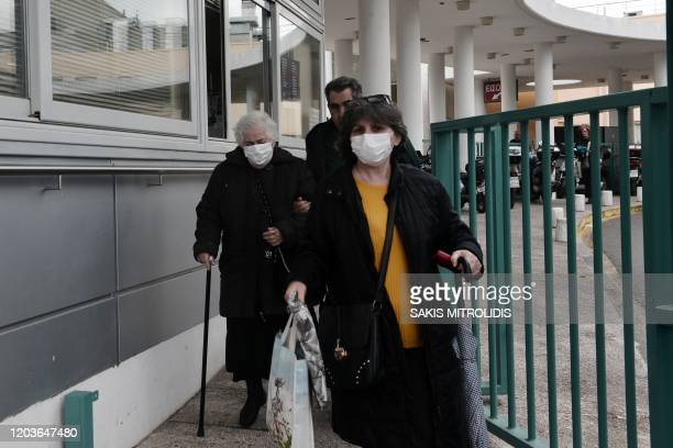 People with protective masks walk outside the hospital of Ahepa in Thessaloniki on February 27 2020 Greece on Februray 26 reported its first...