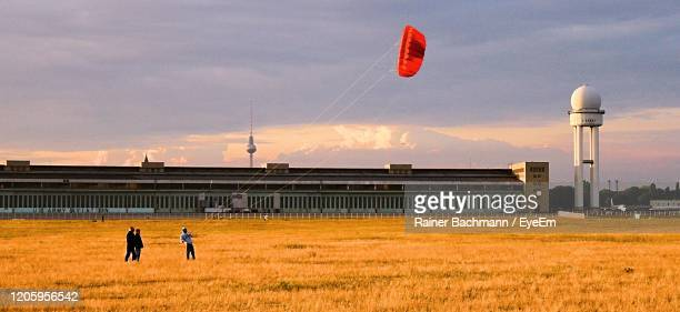 people with red kite on field against sky during sunset - berlin stock pictures, royalty-free photos & images