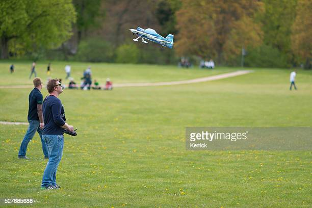People with remote controllers and airplane at model aircraft show