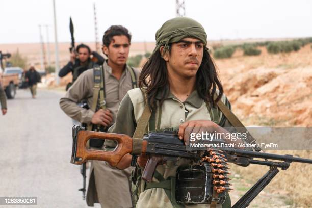 people with rifles and ammunition walking on road - extremism stock pictures, royalty-free photos & images
