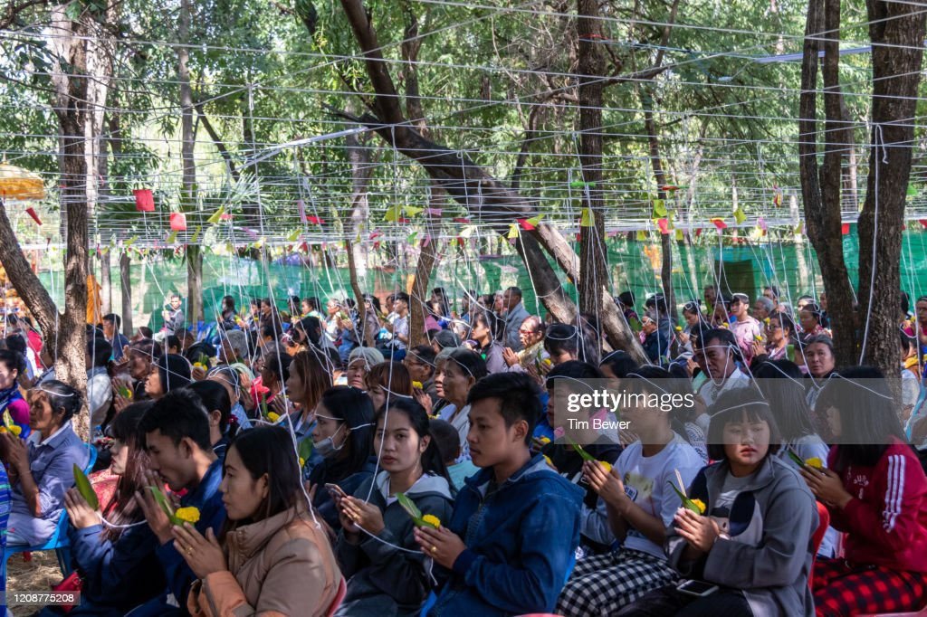 People with sacred threads on their heads during Buddhist ceremony. : Stock Photo