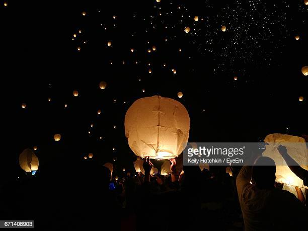 people with sky lantern during festival at night - lantern festival stock photos and pictures