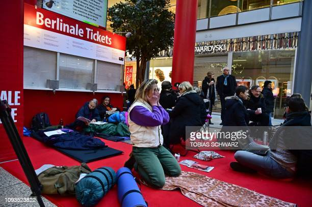 People with sleeping bags wait in front of a still closed sales booth for the presale of tickets for the Berlinale film festival in a shoppping mall...