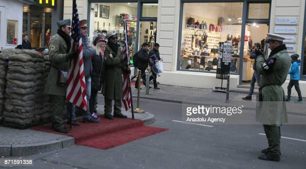 People with soldier uniforms pose for a photo on the 27th anniversary of the fall of the Berlin Wall at Checkpoint Charlie in Berlin Germany on...