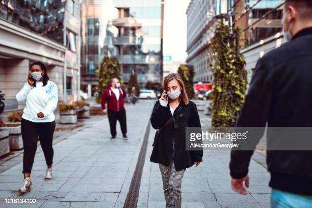 people with surgical masks for covid-19 protection keeping distance while walking - distant stock pictures, royalty-free photos & images