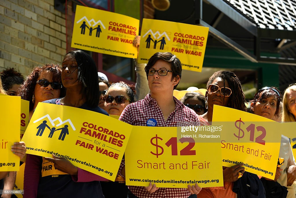 People with the Colorado Families for a Fair Wage campaign hold up signs during their rally on the outdoor patio at Vine Street Pub on May 18, 2016 in Denver, Colorado. Members from the campaign were announcing the kick off for their campaign to get a ballot initiative that would raise the state minimum wage from $6.85 to $12.00 and hour. The campaign is made up of different local non-profits as well people who would be directly impacted by the increase to the minimum wage.