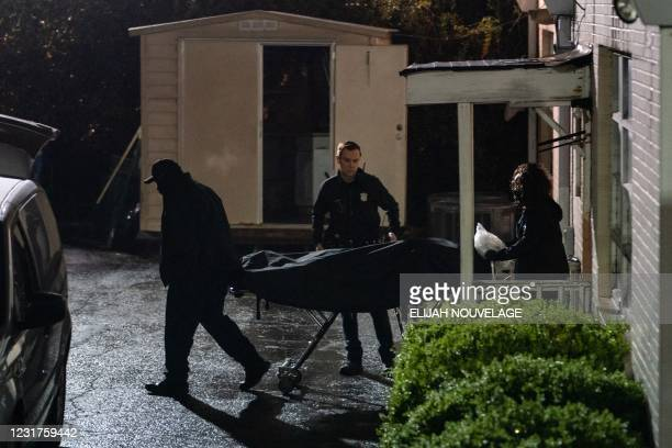 People with the medical examiner's office wheel out a body on a stretcher from a massage parlor where three people were shot and killed on March 16...