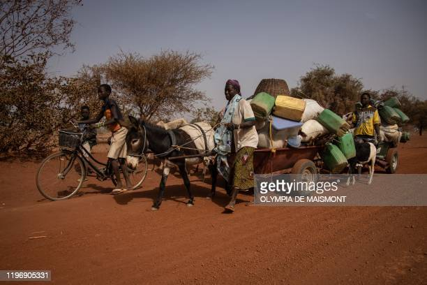 People with their belongings piled on a makeshift trailer pulled by a donkey flee their villages on the road from Barsalogho to Kaya on January 27...