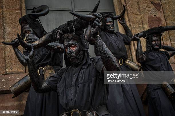 People with their face covered in oil and soot and carrying bull horns representing a devil join a carnival festival on February 14 2015 in Luzon...