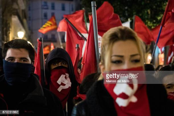 People with their face covered with soviet hammer and sickle during a demonstration for the 100th anniversary of the October Revolution