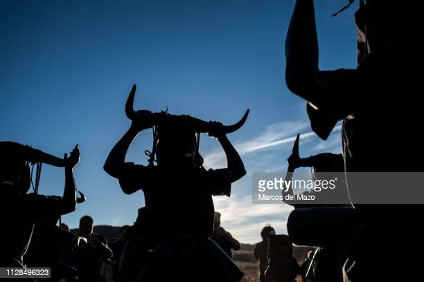 People with their faces covered in oil and soot and carrying bull horns representing a devil during a traditional carnival festival Every year Luzon...
