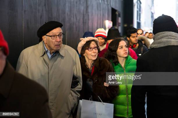 People with Trump's store bag walk along Fifth Avenue on Christmas day on December 25 2017 in New York City Security in New York is on alert as...