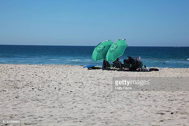 People with two green umbrellas at the beach