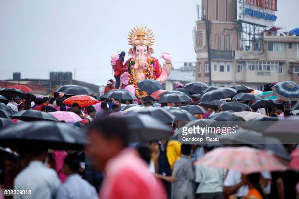 people with umbrella gathered to watch ganesh idol immersion - ganesh chaturthi stock photos and pictures